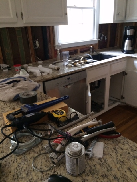 Beautiful new counters underneath a pile of not-the-right-size plumbing parts.